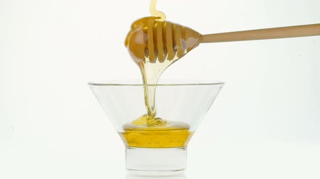 daldırma : Glass bowl with pouring honey and wooden stick dipper on white background