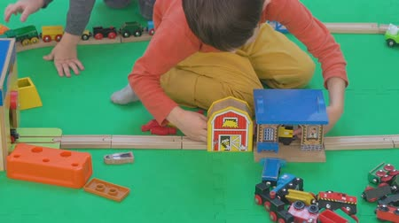 przedszkole : Little boy playing with wooden railway on the floor