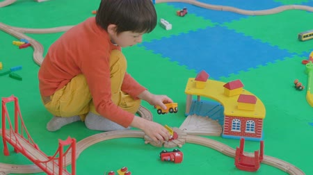 mozdony : Little boy playing with wooden railway on the floor