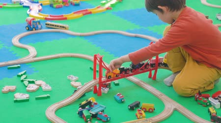 mozdony : Five years old boy playing with wooden railway on the floor in the childrens room