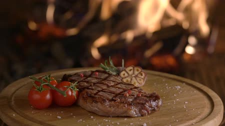 fireside : Rotating grilled beef steak on wooden board on fireplace background Stock Footage