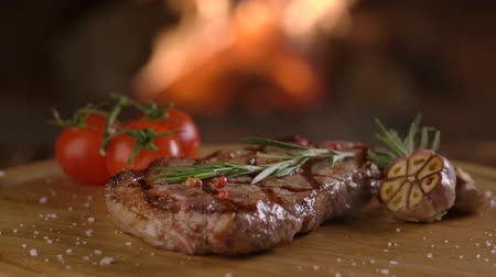 petržel : Rotating grilled beef steak on wooden board on fireplace background Dostupné videozáznamy