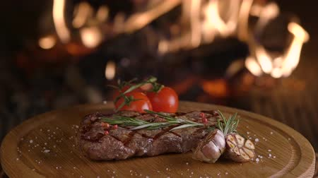 wołowina : Tasty grilled beef steak on wooden board on fireplace background