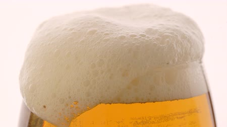 fabricado cerveja : Glass of beer with froth in slow motion on white background