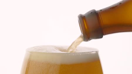 cidra : Slow motion beer pouring into glass from brown bottle over white background
