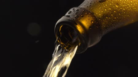cidra : Beer pouring into glass from brown bottle in slow motion on black background