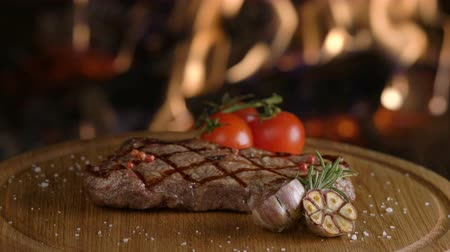 american cuisine : Rotating grilled beef steak on wooden board on fireplace background Stock Footage