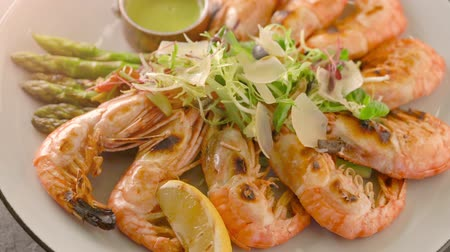 нарезанный : Top view of roasted shrimps served with asparagus and lemon on white plate