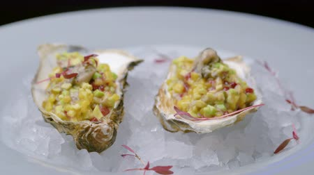 ostrygi : Fresh oysters in crushed ice on a white plate