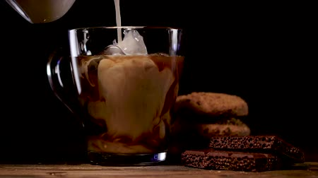 občerstvení : Pouring milk into glass of cold brew coffee on dark background Dostupné videozáznamy