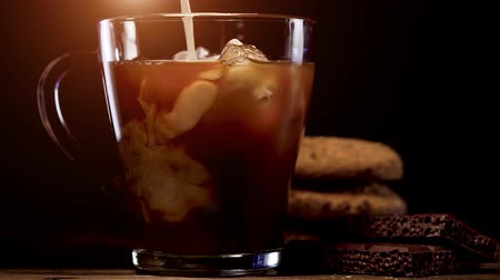 občerstvení : Cold brew coffee with ice and milk on black background Dostupné videozáznamy