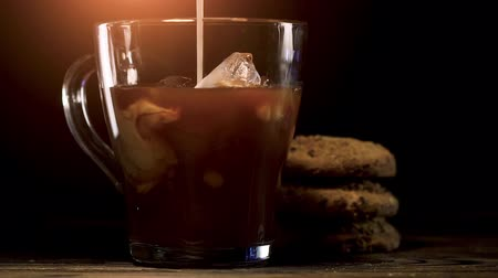 aromatik : Pouring milk into glass of cold brew coffee on dark background Stok Video