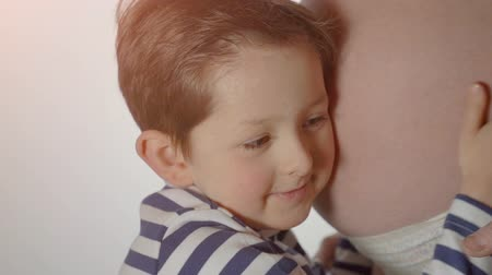 kids : Little boy hugging mothers pregnant belly