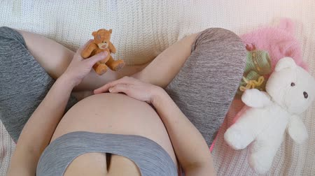 meg nem született : Pregnant Woman holding small teddy bear for her baby, Maternity or motherhood concept Stock mozgókép