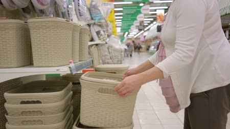 покупатель : Pregnant woman is choosing plastic storage container in supermarket store