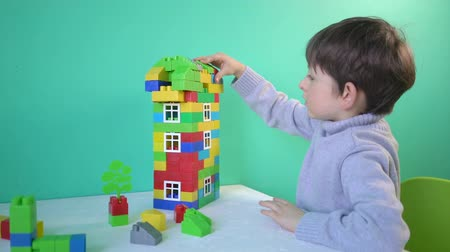 construtor : Little child playing with blocks. Boy sitting on the chair at table and building a house