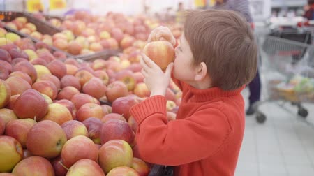 carrello spesa : Funny little boy picking apple from the box, during family shopping in hypermarket