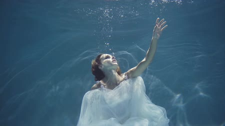 plavat : Young blonde woman in vintage white dress swim underwater