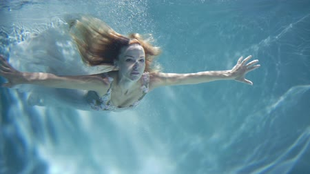 fürdés : A woman in a white dress as a mermaid swimming under water.