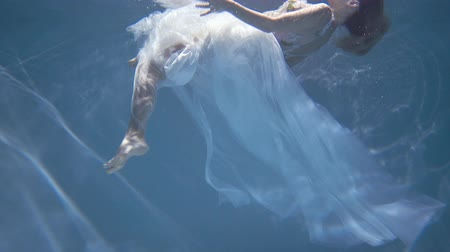 derű : Young blonde woman in vintage white dress swim underwater