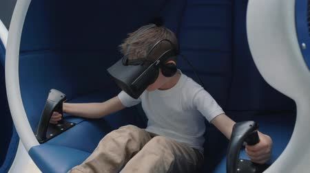 wizja : Boy enjoying virtual reality attraction using VR headset in a moving interactive chair