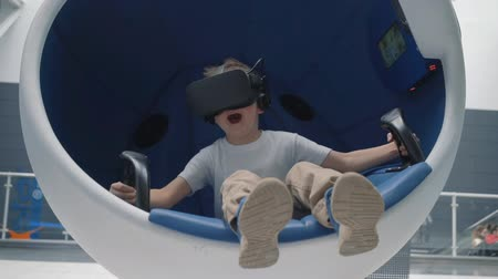 wizja : Boy in a virtual reality headset in a moving interactive chair Wideo