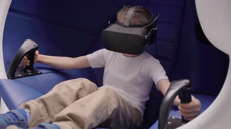 wizja : Little boy playing virtual reality in a moving interactive chair