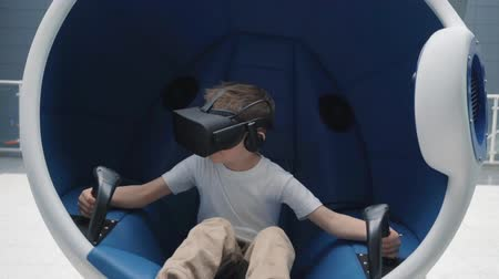 経験 : Boy enjoying virtual reality attraction using VR headset in a moving interactive chair