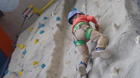 rock wall : little boy climbing a rock wall in a harness indoor. Concept of sport life.