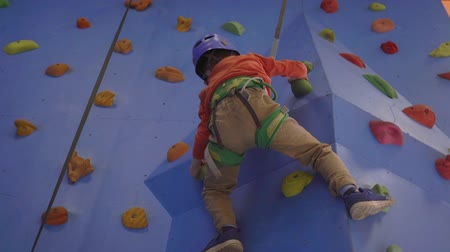 plac zabaw : Activity of rock-climbing on artificial climbing walls, Caucasian boy in a harness climbing a wall with grips