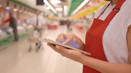 rabat : Female sales clerk wearing red apron using a digital tablet with customers and shelves on background Wideo