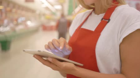 rabat : Female supermarket clerk using apps on a digital tablet, innovative technology and work concept,