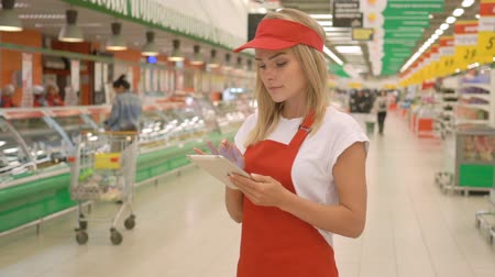 supermarket food : Female sales clerk wearing red apron using a digital tablet with customers and shelfs on background