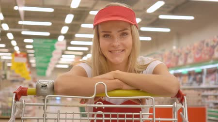 liste : Smiling saleswoman in red uniform leaning on a shopping cart and looking at the camera