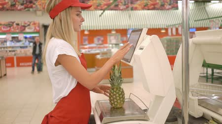 tartmak : Saleswoman in red apron weighing fresh pineapple on electronic scales with touch screen in supermarket