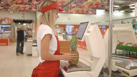 wegen : Jonge vrouwelijke verkoper in rode schort met een gewicht van verse ananas op elektronische weegschalen met touchscreen in de supermarkt Stockvideo