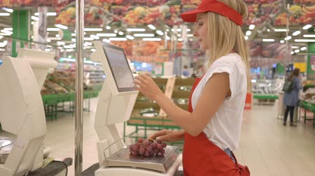 tartmak : Female staff in red uniform weighing grape on electronic scales with touch screen in supermarket