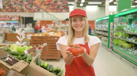 rabat : Young female sales clerk smiling and holding fresh tomatoes at supermarket.