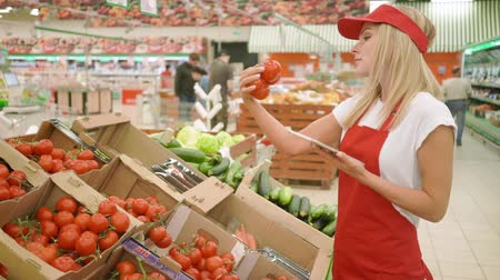 scaffale supermercato : Supermarket clerk working on digital tablet and Checking the quality of the product