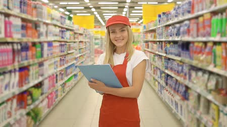 lojas : Female supermarket employee in red uniform holding a clipboard in front of shelf in supermarket