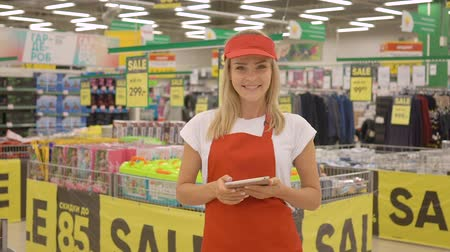 burza cenných papírů : Female seller in a red apron holding digital tablet and looking at the camera