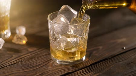 občerstvení : Barman pouring whiskey in a glass with ice on a wooden table