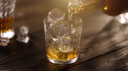občerstvení : Pouring whisky from bottle in to glass with ice cubes, served on rustic wooden table