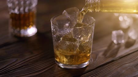 maltês : Bartender pouring whisky from bottle in to glass on rustic wooden table Stock Footage