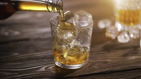 жесткий : Whisky with ice on a wooden table Стоковые видеозаписи
