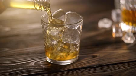бутылки : Bartender pouring whisky from bottle in to glass on rustic wooden table Стоковые видеозаписи