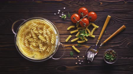 kluski : Cinemagraph - fusilli pasta cooking in boiling water in glass pot on wooden table Wideo