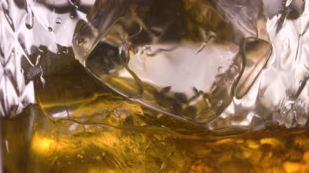 bourbon whisky : Pouring scotch whisky in glass with ice cubes in slow motion Stock mozgókép