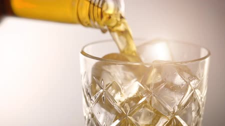 splattered : Pouring scotch whisky in glass with ice cubes in slow motion Stock Footage
