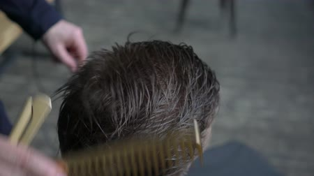 луки : barber makes hair styling with hair gel for customer.